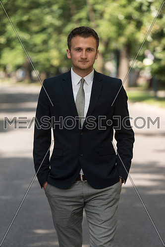 Young Businessman Walking Outdoors In Park While Resting From Office Work