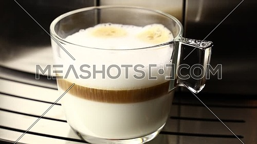 Close up of woman hand taking away ready latte cappuccino coffee in transparent glass cup from automatic coffee machine, low angle view