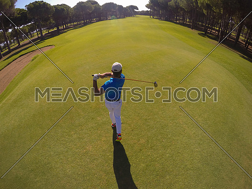 top view of golf player hitting shot with club on course at beautiful morning
