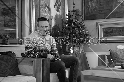 Portrait of a happy young man celebrating winter holidays at home beautifully decorated for Christmas