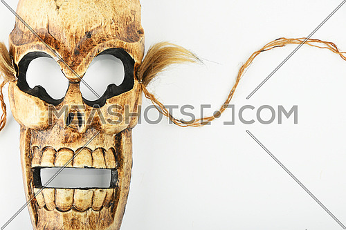 Handmade wooden carved creepy skull death joker mask on white background