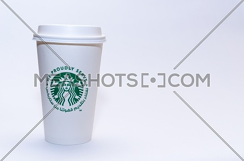 Starbucks coffee cup with Arabic writing saying ( We Proudly Serve Our Coffee from Starbucks) on a white background. December 2018 in Cairo, Egypt