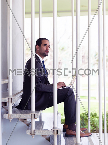 handsome young middle eastern business man working on laptop computer online while sitting on steps in front of modern corporate office building