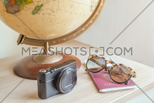 Concept travel, globe, photo camera,sunglasses,ticket airplane and passport on a wooden table. Idea, photo tourism, adventure, travel around the world