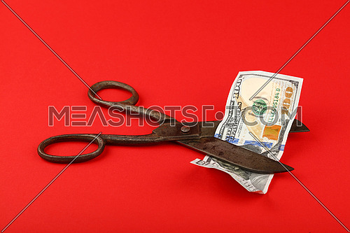 US financial crisis, decline of American economy and dollar exchange rate illustrated, old vintage scissors cut one hundred dollars banknote at over red background, high angle view