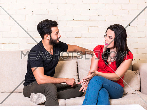 young couple sitting on a sofa in front of white table having fun together