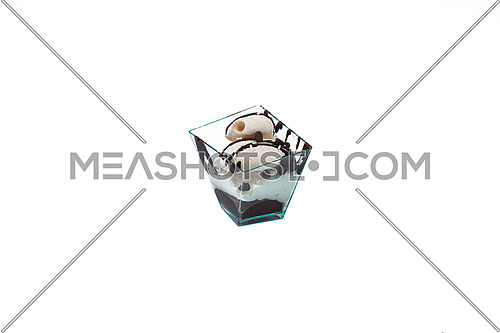 In the picture a cupcake with choccolate and cream in a plastic cup,isolated on white background.