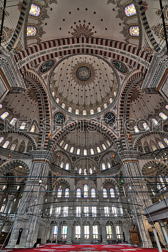 Fatih Mosque, a public Ottoman mosque in the Fatih district of Istanbul, Turkey, low level angled shot showing huge arches, decorated domes and colored stained glass windows