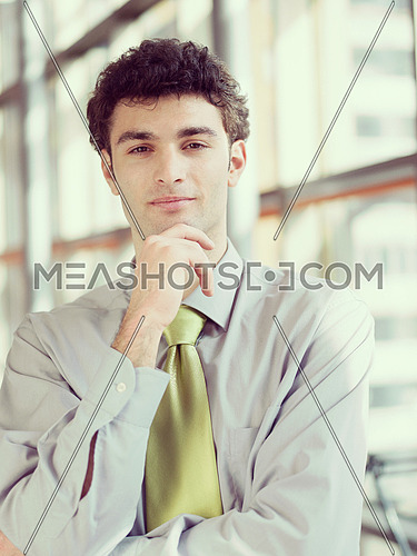 portrait of young business man at modern office  interior with big windows in background
