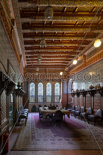 Manial Palace of Prince Mohammed Ali. Dining room at the Residence Building, with ornate wall and ceiling, Big ornate window, built-in wooden decorated cupboards and ornate carpet, Cairo, Egypt