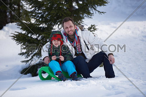 portrait of father and son on snow sitting on sled at beautiful sunny winter day