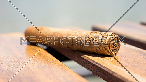 Cuban cigar resting on a wooden surface