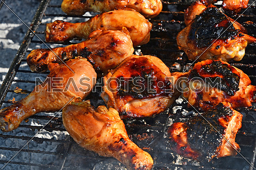Grilled barbeque chicken legs meat portions cooked on fire grill close up