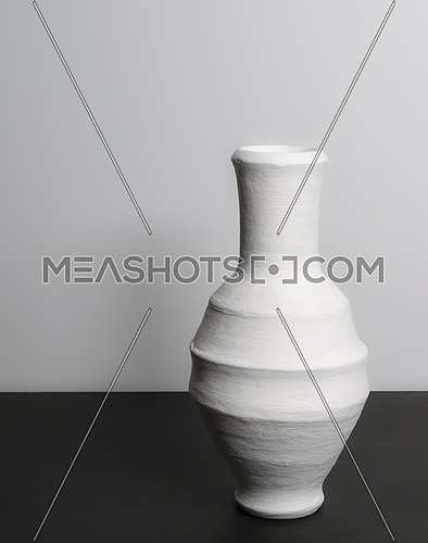 Pottery white vase on black table and white wall