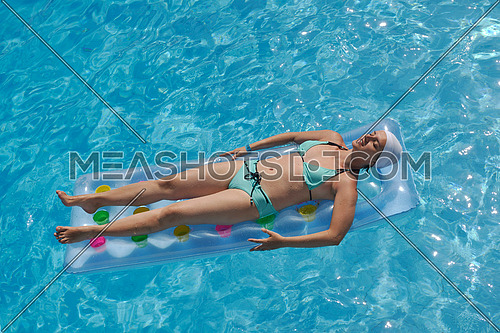 happy young woman relax at swimming pool at vacation travel resort