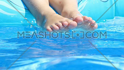 Child's feet at the poolside playing in water under the hot summer sun