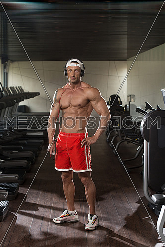 Muscular Mature Man Listening Music From His Mp3 Player In Modern Fitness Center