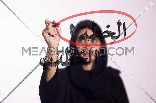 Arabian middle eastern business woman writing with a marker on virtual screen in arabic Plan A & Plan B isolated on white background