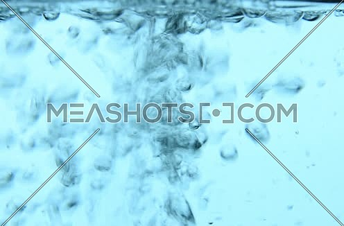 Pouring pure clear cold water in transparent glass jar with bubbles of stream, close up, low angle side view, slow motion