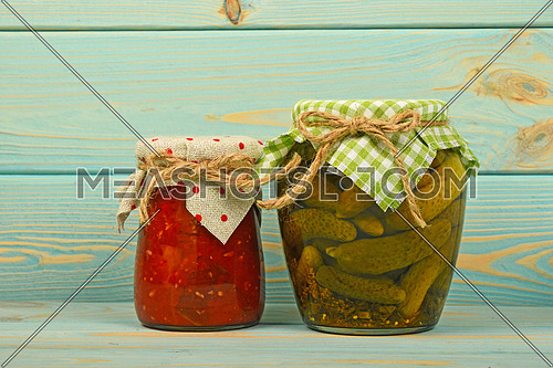 One glass jar of homemade eggplant pepper salad and pickled cucumbers with green checkered textile decoration over blue painted wooden surface