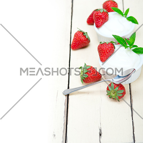 organic Greek yogurt and strawberry over white rustic wood table