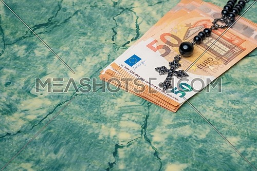 Black rosary and euro money on green table,concept photo.