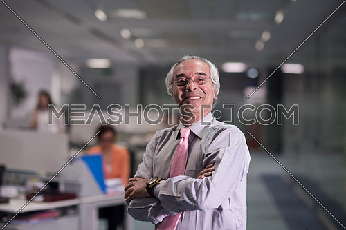 portrait of senior businessman as leader  at modern office interior  young  people group in background on their workplace