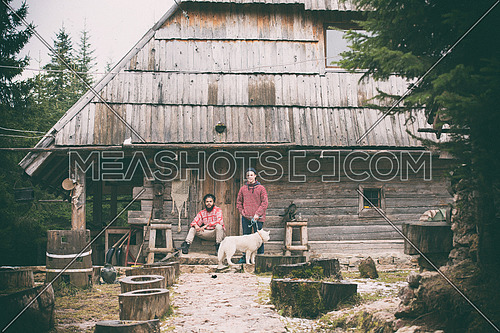 hipsters couple portrait, two young  man with white husky dog  sitting in front of old wooden retro house