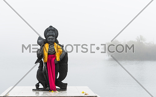 Hindu staue in a temple (Grand Basin), in the day with mist ,create mystical atmosphere.Mauritius