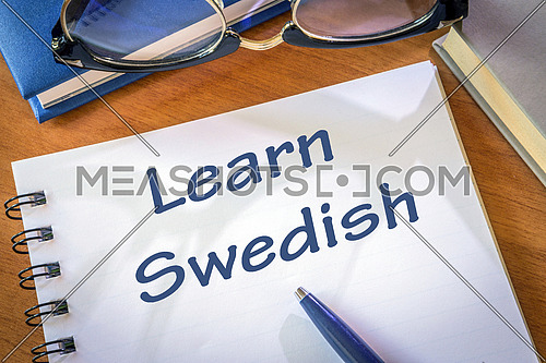 Learn Swedish written in a notepad. Education concept