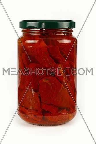 Close up of one glass jar of pickled red sundried cured tomatoes in oil with green lid over white background, low angle side view