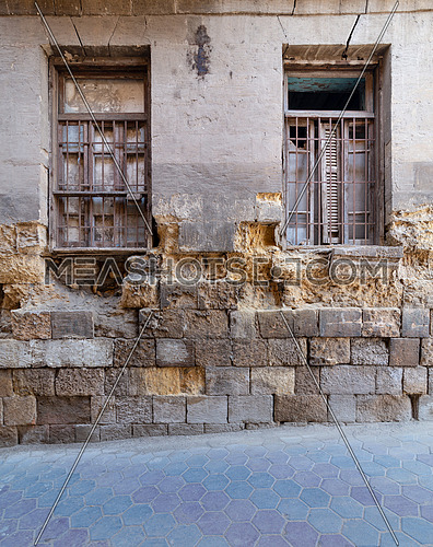 Two adjacent broken windows and grunge stone bricks wall in abandoned Darb El Labana district, Cairo, Egypt