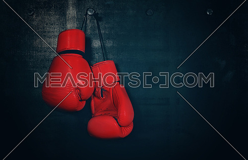 Close up pair of red leather boxing gloves hanging over black wall with copy space