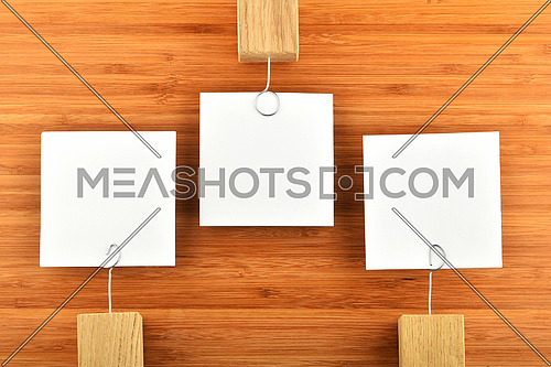 Opposite Opinion - three white paper notes with wooden holders in different directions on wooden bamboo background for presentation