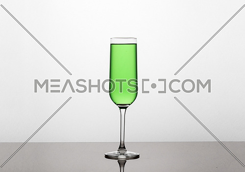 Green liquid in a glass isolated on white