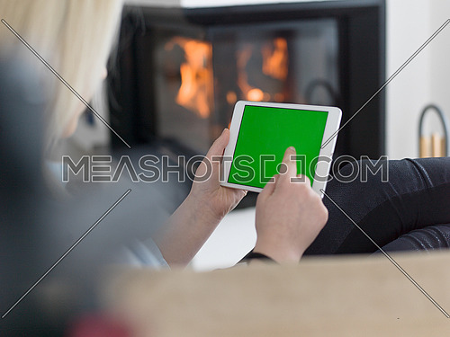beautiful young woman surfing web using tablet computer in front of fireplace on cold winter day at home