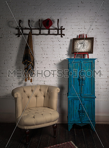 Retro composition of vintage beige armchair, vintage blue cupboard, wall hanger with ornate scarf and red fez, and framed painting in studio
