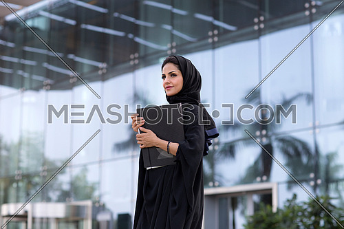 Saudi lady standing and holding a holder, wearing black abaya in front of glass building in background at day.