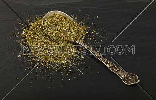 Close up one vintage antique metal spoon full of green dried herbs, dill or marjoram on background of black slate board, high angle view