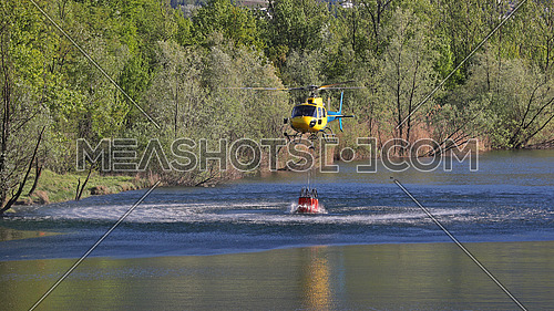 Helicopter picking up water during fire fighting operations