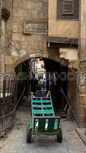A teen worker pulling a trolley through an only arch in the city