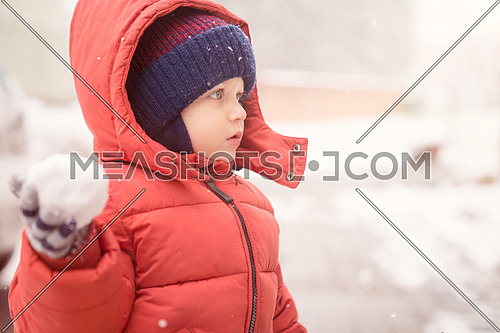 Infant boy while snowing looks towards the emptiness, holding in his hand a snowball, covered with red winter jacket and woolen hat, close-up.