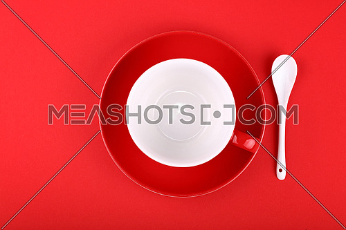 Close up one empty tea or coffee cup and red saucer with white spoon over vivid paper background, elevated top view, directly above