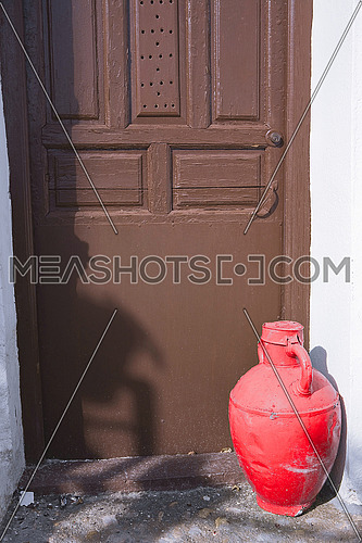 Old door of a house and a jar of red brass