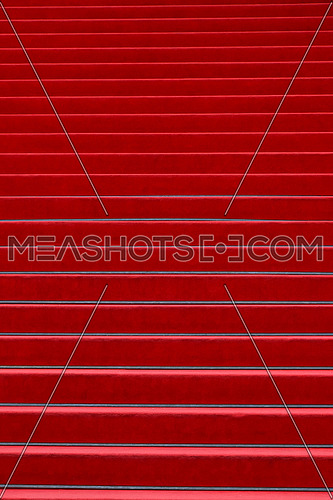 Close up red carpet covered stairs perspective ascending, low angle view