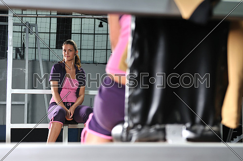 young woman relaxing from working out in a gym by listening music on mp3 player
