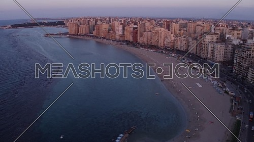 Aerial shot for the Cornich showing the city,  traffic and Montaza Palace in Alexandria City,  Egypt at dusk