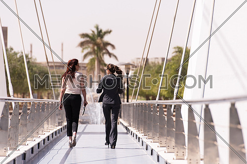 business woman group walking together across modern bridge at early mornig while drinking coffee
