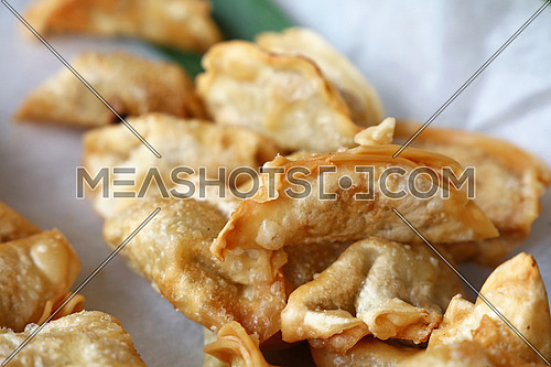 Close up portion of traditional Chinese Jiaozi deep fried dumplings on paper, high angle view
