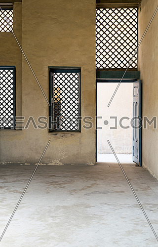 Blue vintage wooden windows with interleaved wooden grid (mashrabiya) and blue wooden door with plaster yellow wall
